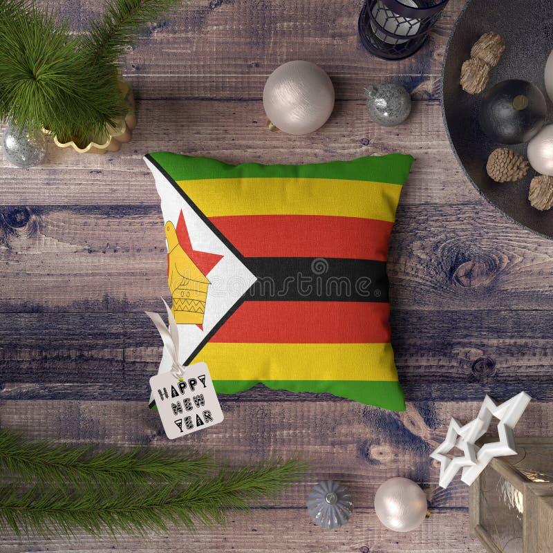 Etichetta del buon anno con la bandiera dello Zimbabwe sul cuscino Concetto della decorazione di Natale sulla tavola di legno con fotografia stock