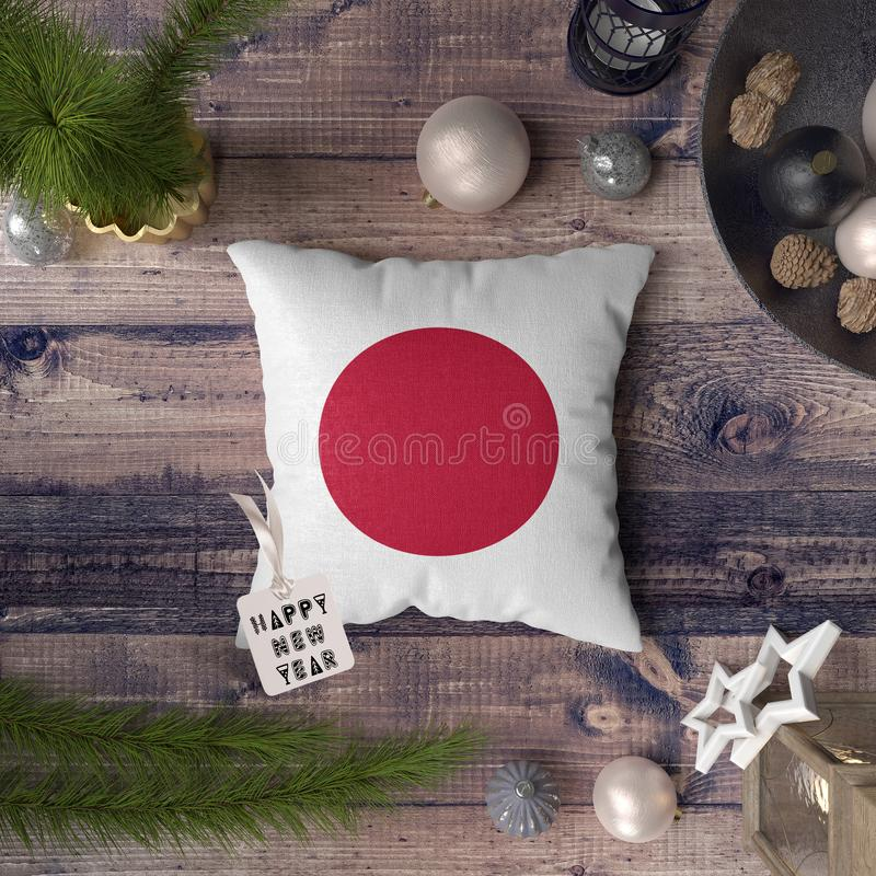 Etichetta del buon anno con la bandiera del Giappone sul cuscino Concetto della decorazione di Natale sulla tavola di legno con g fotografie stock