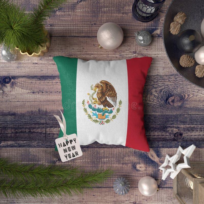 Etichetta del buon anno con la bandiera del Messico sul cuscino Concetto della decorazione di Natale sulla tavola di legno con gl fotografia stock libera da diritti