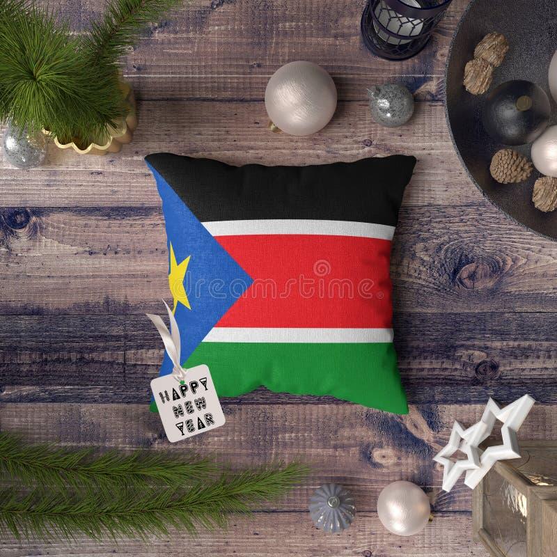 Etichetta del buon anno con la bandiera del sud del Sudan sul cuscino Concetto della decorazione di Natale sulla tavola di legno  immagini stock libere da diritti