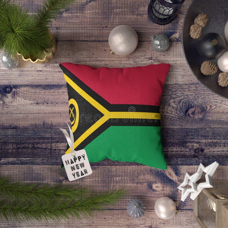 Etichetta del buon anno con la bandiera del Vanuatu sul cuscino Concetto della decorazione di Natale sulla tavola di legno con gl fotografia stock libera da diritti