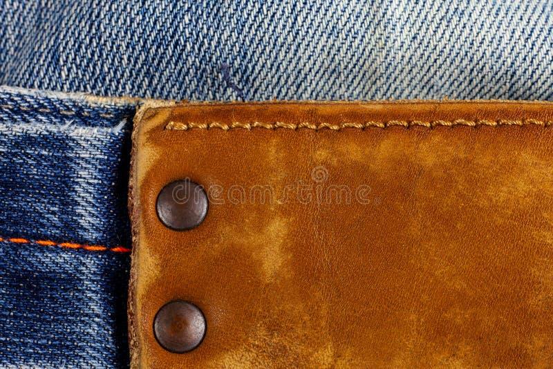 Etichetta del cuoio di Brown sulle blue jeans fotografia stock