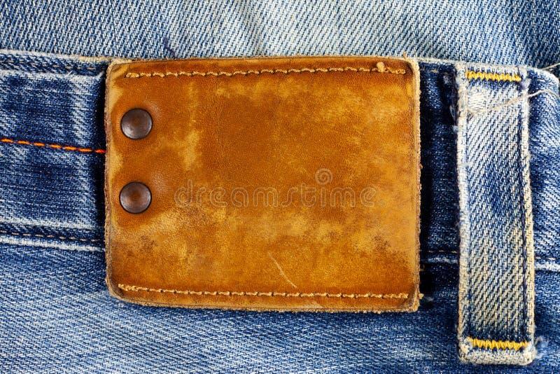 Etichetta del cuoio di Brown sulle blue jeans immagini stock libere da diritti