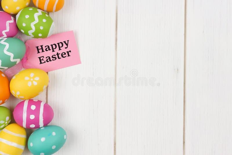 Etichetta del regalo con il confine del lato dell'uovo di Pasqua contro legno bianco fotografia stock