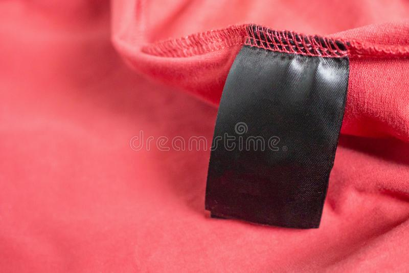 Etichetta dell'abbigliamento di colore del nero dello spazio in bianco sulla maglietta rossa immagini stock libere da diritti