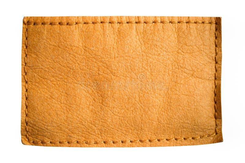 Etichetta di cuoio dell'etichetta dei jeans dello spazio in bianco nel colore giallo marrone chiaro con chiaro spazio vuoto per t fotografie stock