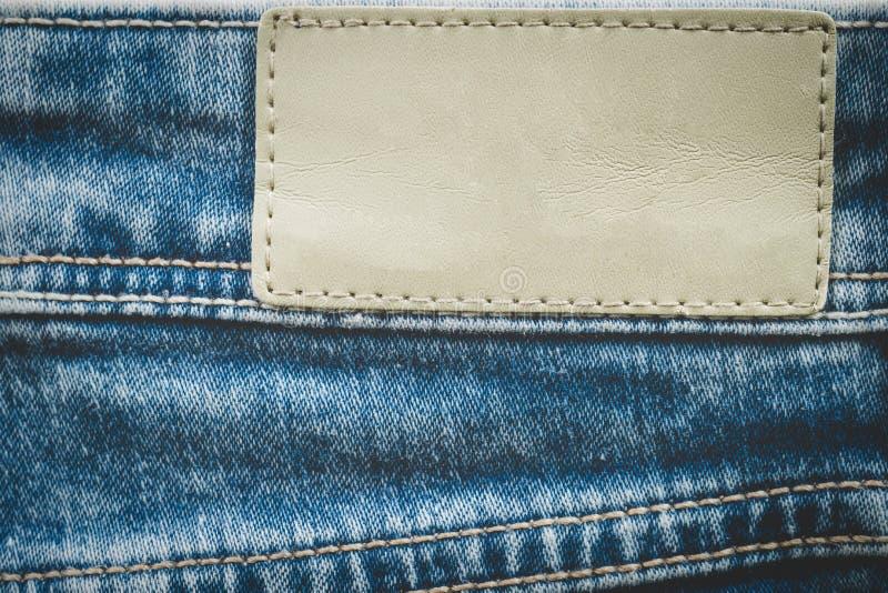 Etichetta di cuoio vuota sul fondo dei jeans con lo spazio della copia fotografie stock