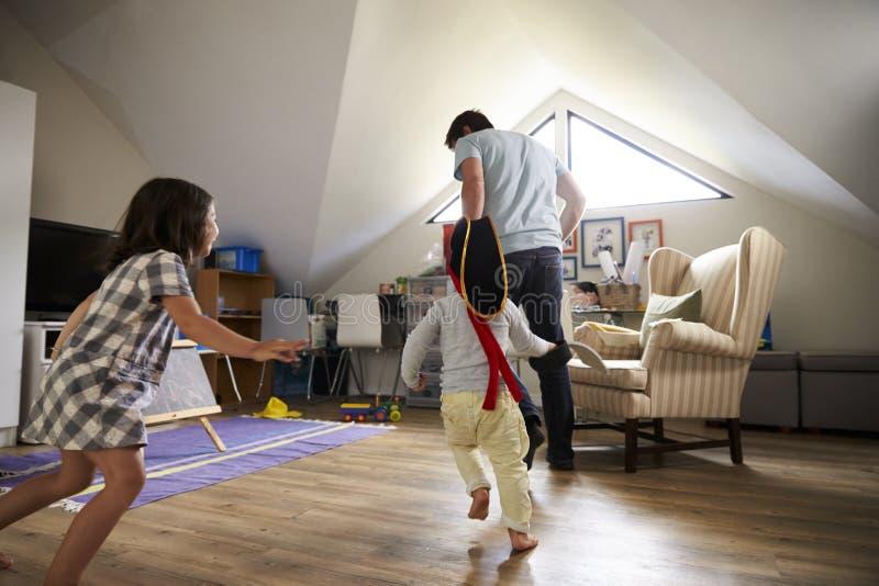 Etichetta di Having Game Of del padre con i bambini in stanza dei giochi immagine stock libera da diritti