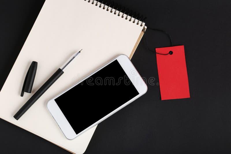 Etichetta di vendita con il taccuino e lo smartphone immagini stock