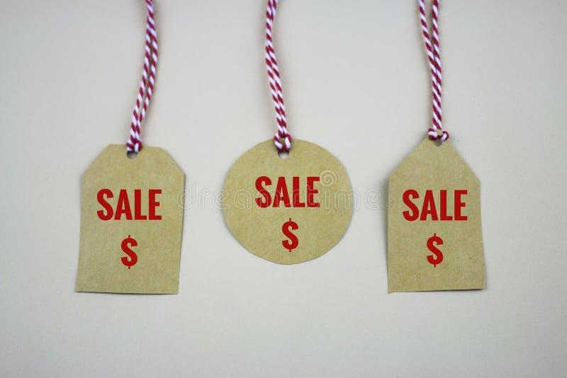 Etichette d'attaccatura delle etichette di vendita sulla tavola bianca immagine stock