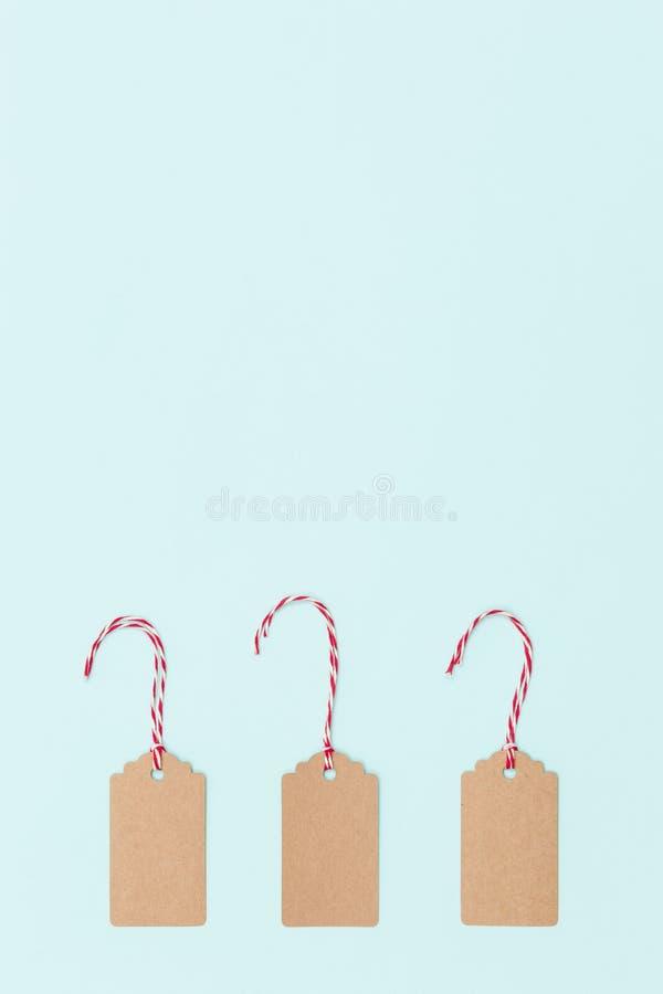 Etichette di Natale in cartone normale con corda rossa e corda bianca su fondo blu-chiaro Buon Natale fotografie stock libere da diritti