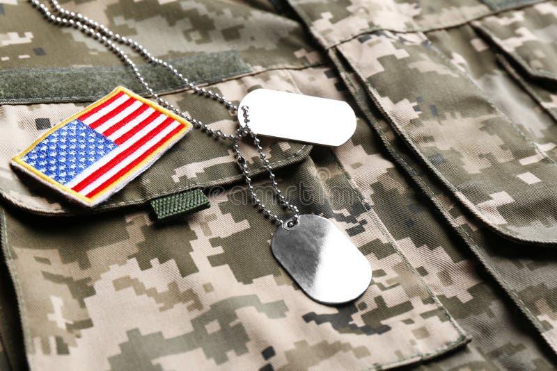 Etichette militari di identificazione e toppa della bandiera dell'esercito americano su cammuffamento fotografia stock libera da diritti