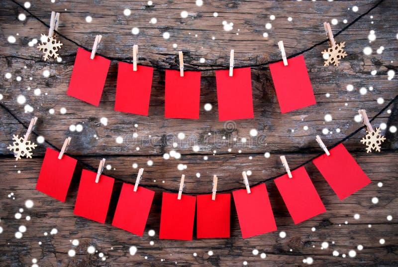 Etichette rosse con lo spazio della copia che appende nella neve su fondo di legno immagine stock libera da diritti