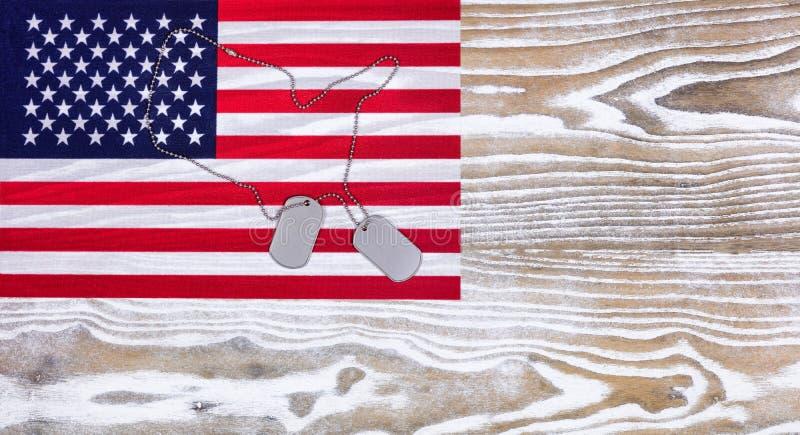 Etiketter för USA flagga- och militärlegitimation bleknar på vit wood bakgrund royaltyfri bild