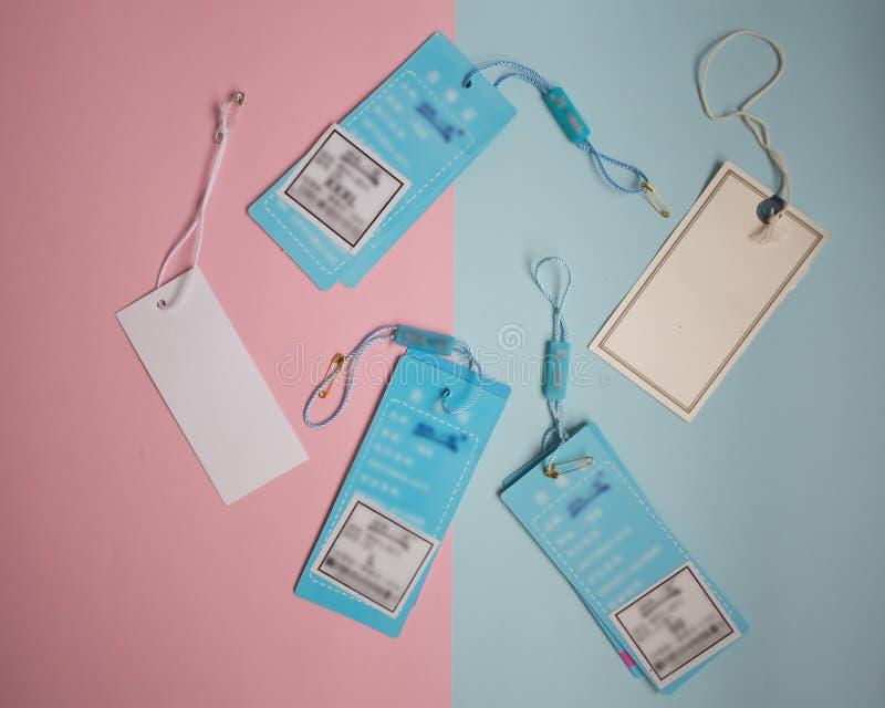 etiketter från kläder på rosa och blå bakgrund arkivfoto