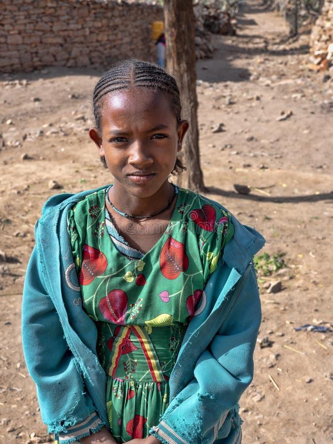ETIOPIEN APRIL 28th 2019 etiopisk flicka i berg i den gröna klänningen, April 28th 201 Etiopien arkivbild