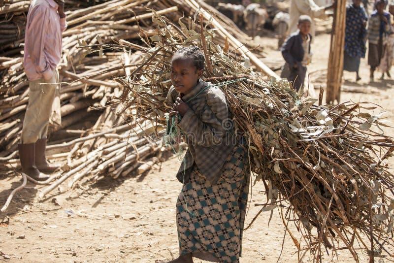 Etiopisk flicka som bär den tunga påfyllningen royaltyfria foton