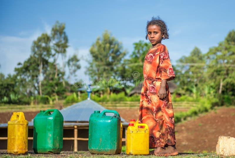 Etiopisk flicka som går för vatten nära Addis Ababa, Etiopien arkivfoto