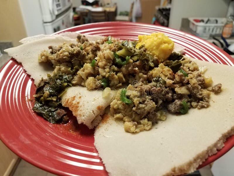 Etiopska karmowa korzenna wo?owina, jelito i chleb na czerwie? talerzu w kuchni obraz royalty free