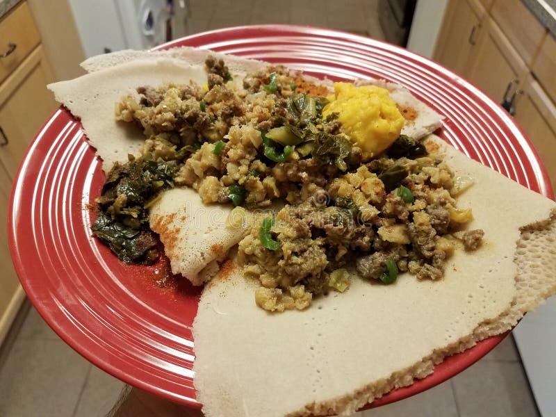 Etiopska karmowa korzenna wo?owina, jelito i chleb na czerwie? talerzu w kuchni zdjęcia stock