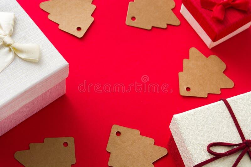 Etiqueta branca da árvore da caixa de presente e de Natal no fundo vermelho imagem de stock royalty free
