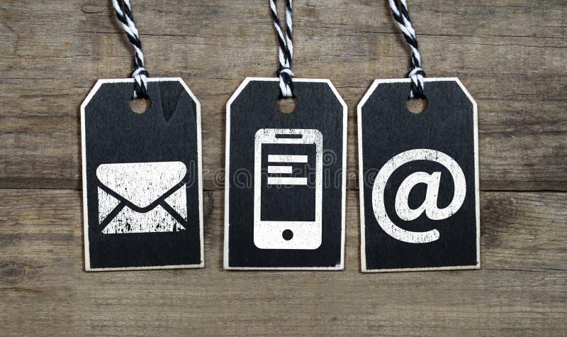Etiqueta colgante de madera negra con los iconos de la atención al cliente fotos de archivo libres de regalías