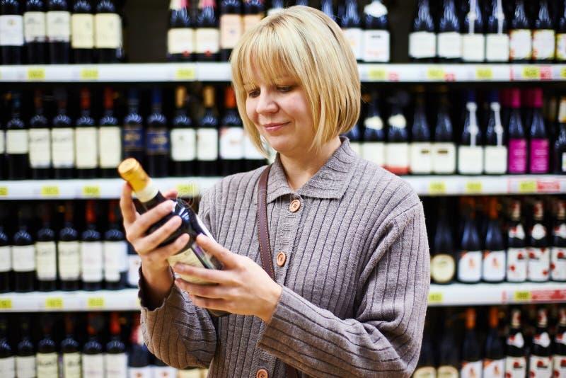 Etiqueta da leitura da mulher na garrafa do vinho na loja imagem de stock royalty free