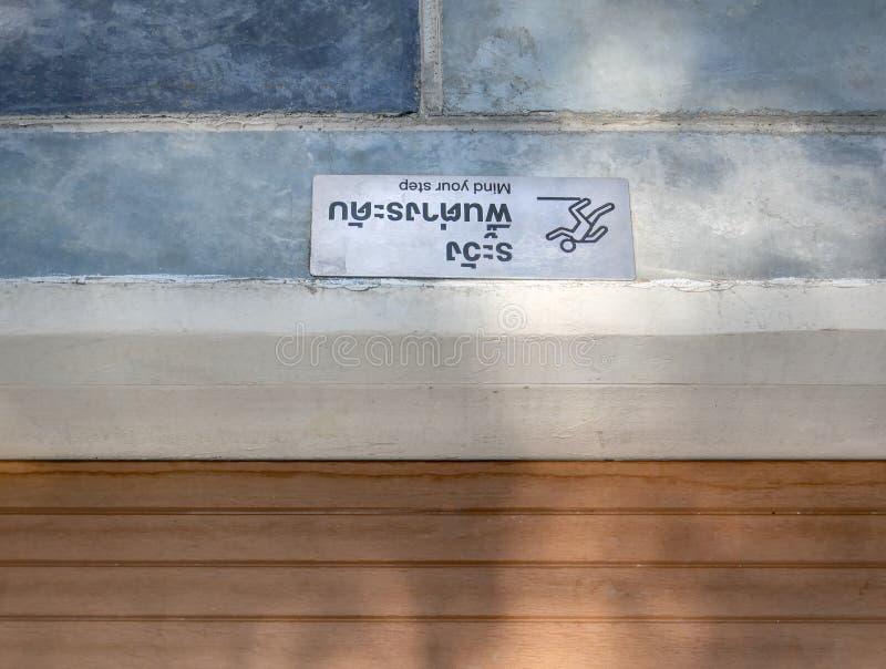 Etiqueta de advertencia de la mente su paso en tailandés e inglés fotografía de archivo