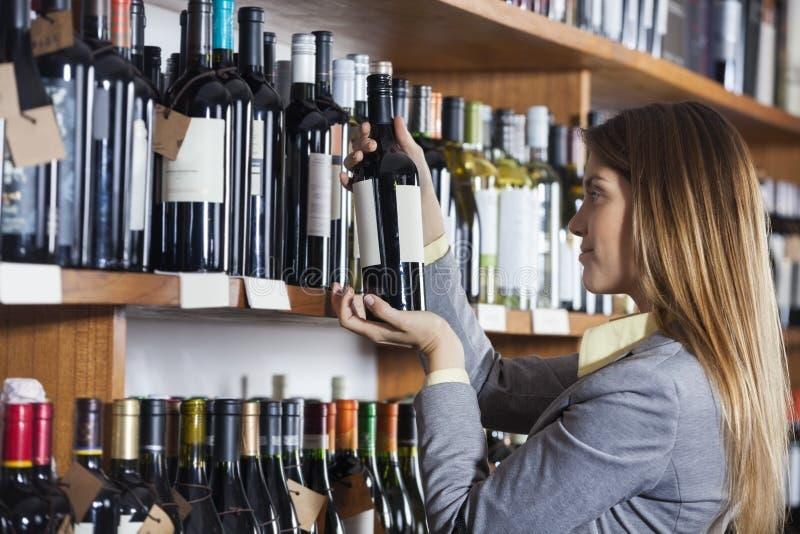 A etiqueta de garrafa de vinho da leitura da mulher na loja fotografia de stock royalty free