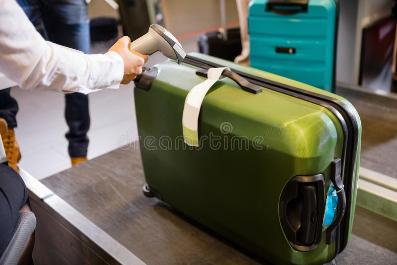 Etiqueta de la exploración de la mujer en el equipaje en el enregistramiento del aeropuerto foto de archivo