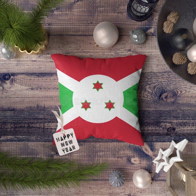 Etiqueta de la Feliz Año Nuevo con la bandera de Burundi en la almohada Concepto de la decoraci?n de la Navidad en la tabla de ma fotografía de archivo