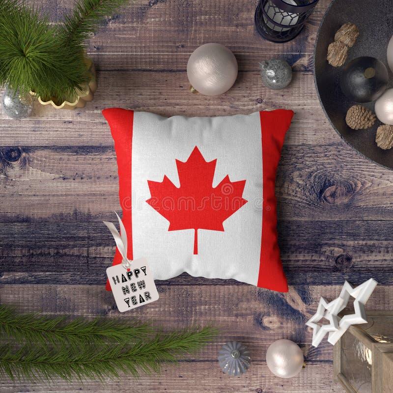 Etiqueta de la Feliz Año Nuevo con la bandera de Canadá en la almohada Concepto de la decoraci?n de la Navidad en la tabla de mad imagen de archivo libre de regalías