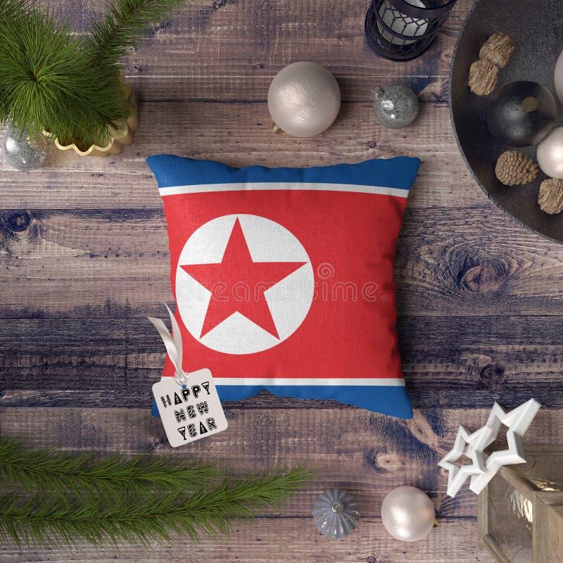 Etiqueta de la Feliz Año Nuevo con la bandera de Corea del Norte en la almohada Concepto de la decoraci?n de la Navidad en la tab fotos de archivo libres de regalías
