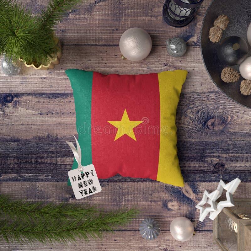 Etiqueta de la Feliz Año Nuevo con la bandera del Camerún en la almohada Concepto de la decoraci?n de la Navidad en la tabla de m fotos de archivo