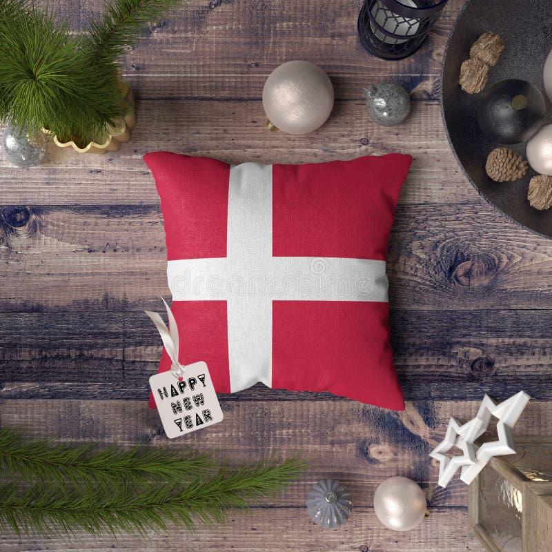 Etiqueta de la Feliz Año Nuevo con la bandera de Dinamarca en la almohada Concepto de la decoraci?n de la Navidad en la tabla de  foto de archivo