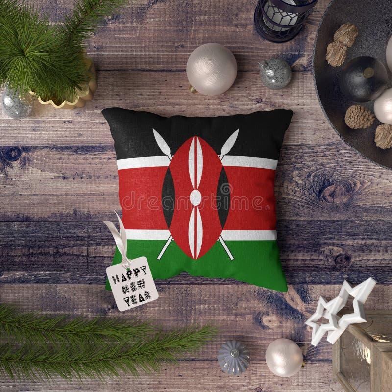 Etiqueta de la Feliz Año Nuevo con la bandera de Kenia en la almohada Concepto de la decoraci?n de la Navidad en la tabla de made imagen de archivo libre de regalías