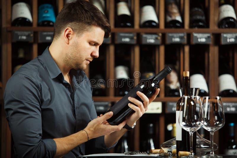 Etiqueta de la lectura del Sommelier de la botella de vino en manos imágenes de archivo libres de regalías