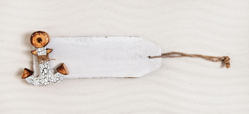 Etiqueta de madeira branca com uma âncora na areia Anunciando a placa imagem de stock