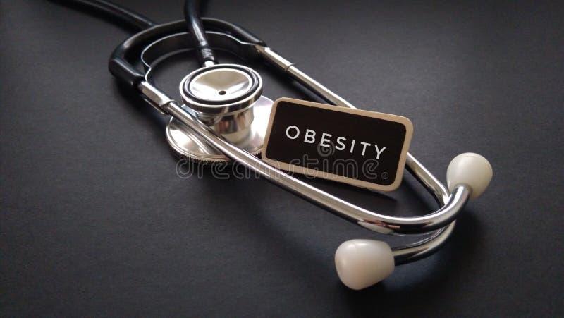 Etiqueta de madera escrita con OBESIDAD y el estetoscopio en fondo negro Concepto médico y de la atención sanitaria imagen de archivo