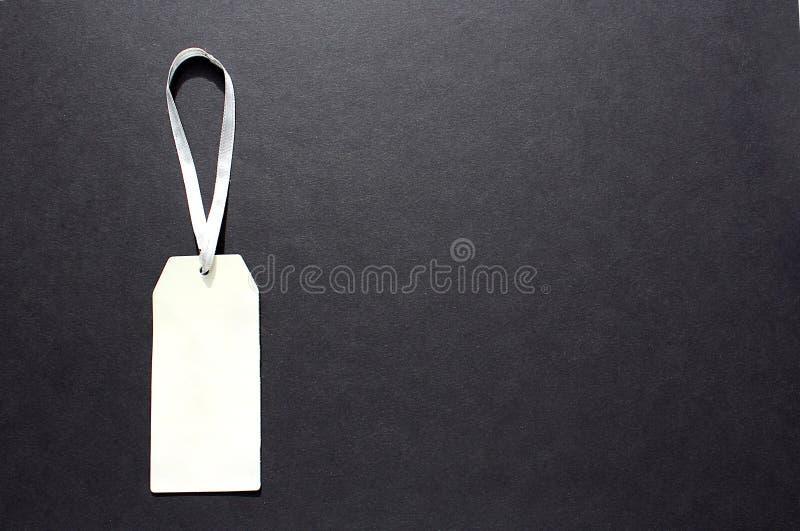Etiqueta de papel para a roupa em um fundo preto fotos de stock royalty free