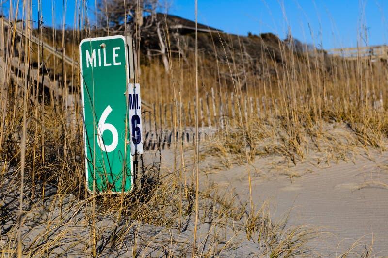 Etiqueta de plástico de la milla en la playa fotos de archivo libres de regalías