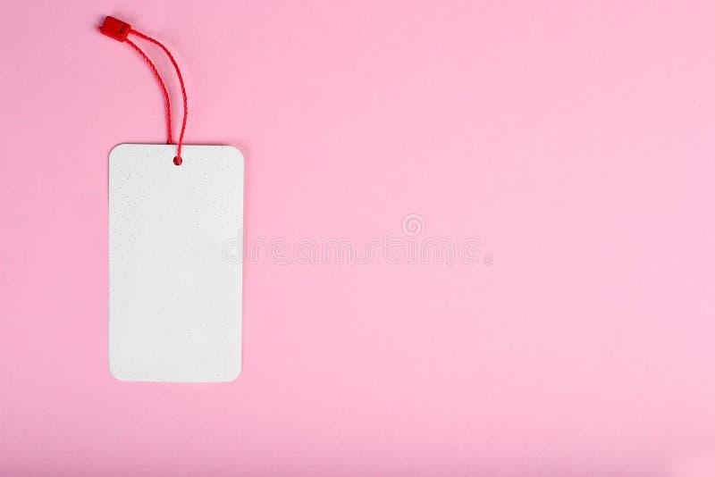 Etiqueta decorativa de la cartulina del espacio en blanco con el lazo rojo de la guita, en fondo rosado fotografía de archivo