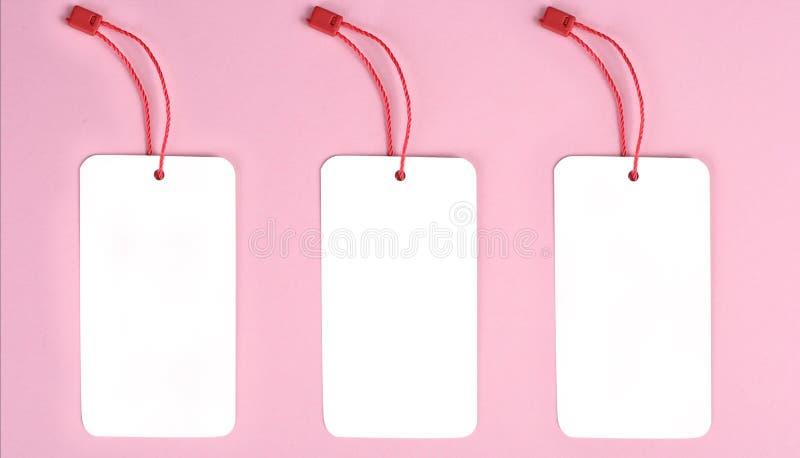 Etiqueta decorativa en blanco de la cartulina tres con el lazo rojo de la guita, en fondo rosado Mofa para arriba imágenes de archivo libres de regalías