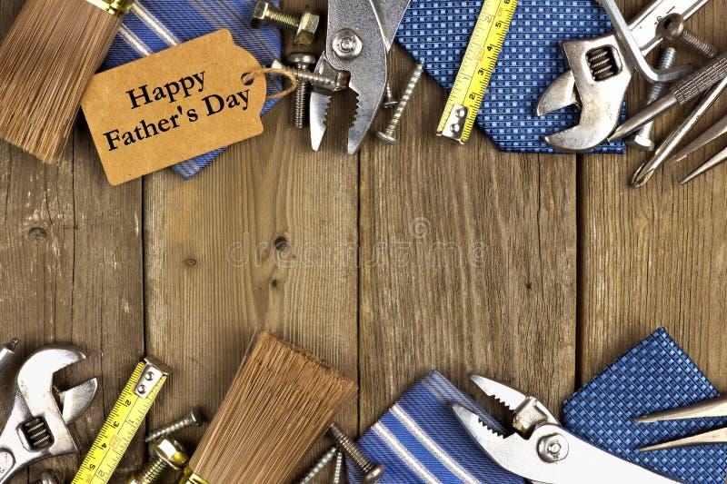 Etiqueta del día de padres con las herramientas y marco de los lazos en la madera imagenes de archivo