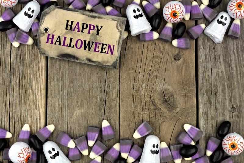Etiqueta del feliz Halloween con la frontera del doble del caramelo sobre la madera envejecida fotografía de archivo libre de regalías