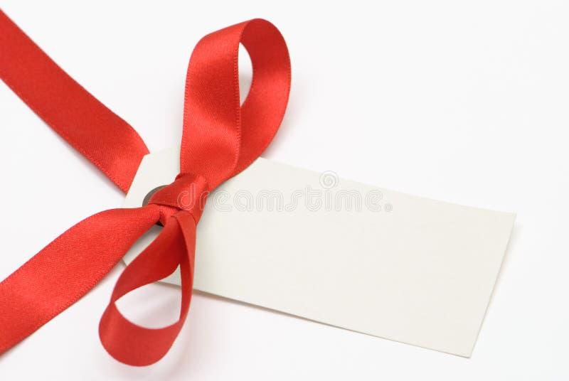 Etiqueta del regalo con la cinta roja foto de archivo libre de regalías