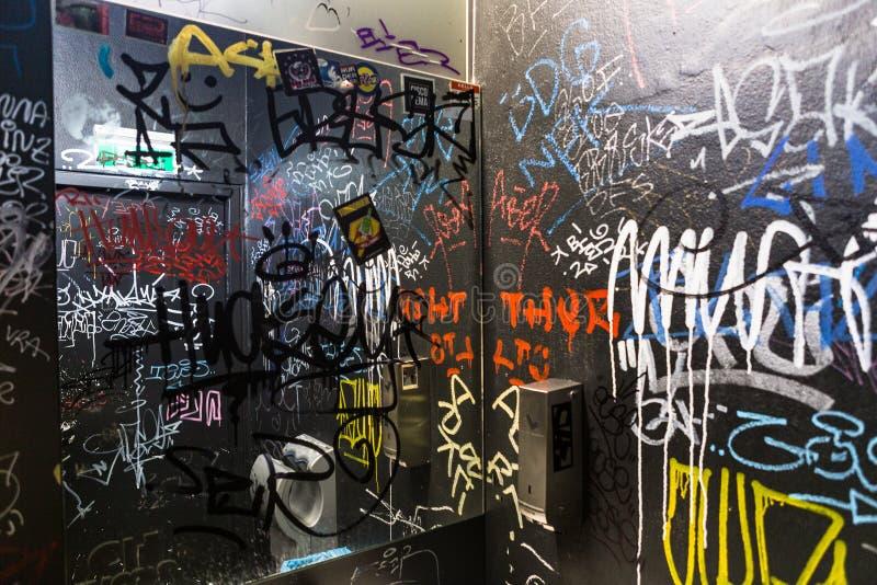 Etiqueta del vandalismo de la pintada que escribe color de texto interior de la pared del lavabo del retrete del WC imágenes de archivo libres de regalías