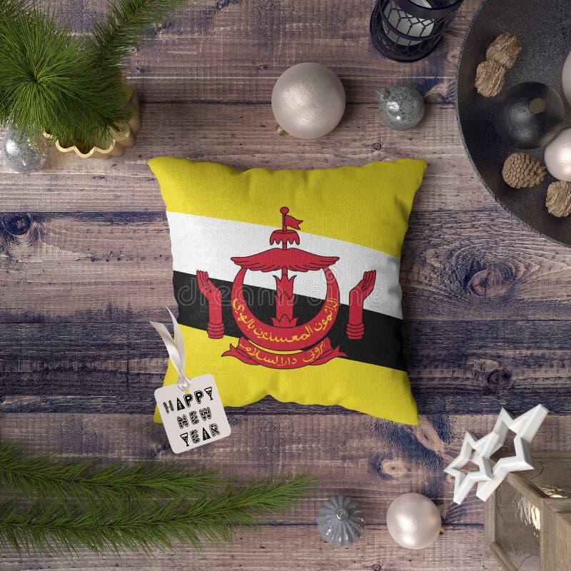 Etiqueta do ano novo feliz com a bandeira de Brunei Darussalam no descanso Conceito da decora??o do Natal na tabela de madeira co imagem de stock
