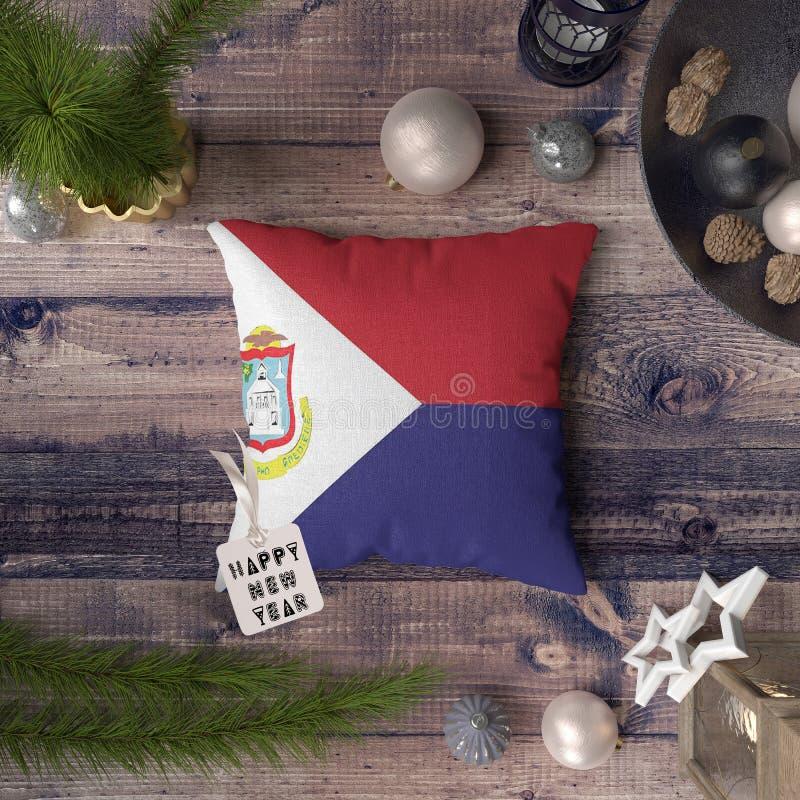 Etiqueta do ano novo feliz com a bandeira de Saint Martin no descanso Conceito da decora??o do Natal na tabela de madeira com obj fotografia de stock royalty free