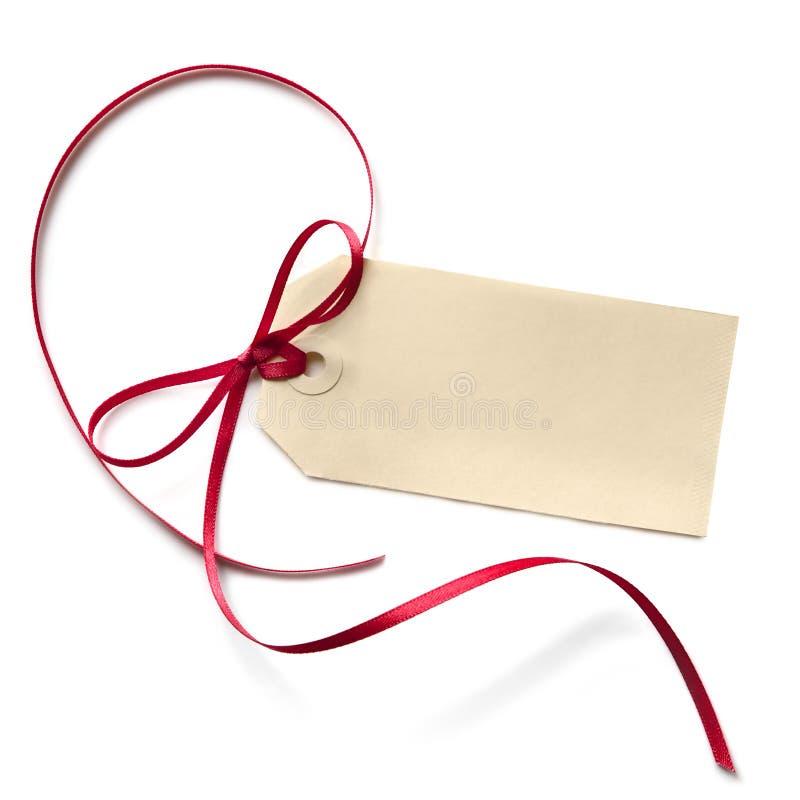 Etiqueta en blanco del regalo con la cinta roja imagen de archivo libre de regalías
